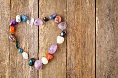 Gestolperte heilende Kristalle im Herzen formen auf hölzernen Hintergrund Stockfotografie