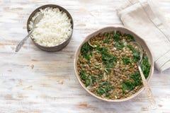 Gestoofde boerenkoollinzen met uien en knoflook op een lichte achtergrond Stock Foto