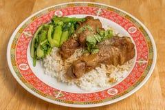 Gestoofde kip of Gesmoorde kip met Chinese boerenkool en rijst in schotel op houten lijst royalty-vrije stock fotografie