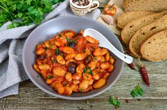 Gestoofde tuinbonen in tomatensaus met kruiden en kruidenclose-up, plakken van roggebrood stock fotografie