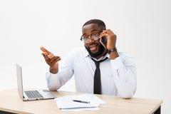 Gestor de escritório afro-americano focalizado que senta-se no escritório com o portátil, lendo documentos importantes com confun fotografia de stock
