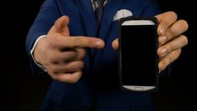 Gestor de escritório elegante que aponta na exposição esperta do telefone vídeos de arquivo