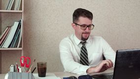 Gestor de escritório masculino com a barba e os vidros, trabalhando atrás de um portátil vídeos de arquivo
