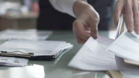 Gestor de escritório masculino que verifica originais na tabela e que enche o relatório financeiro filme