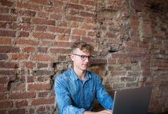 Gestor de inversiones digital experto del hombre joven que trabaja en el ordenador portátil, sentándose en interior moderno Fotografía de archivo