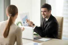 Gestor de projeto feliz que mostra o relatório financeiro, stats de aumentação, GR Imagens de Stock Royalty Free