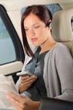 Gestore esecutivo della donna che si siede automobile nel chiamare Fotografia Stock