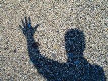 Gestos de la silueta de la mano en fondo del arena de mar imágenes de archivo libres de regalías