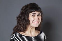 Gestraffte junge Brunettefrau, die erschrocken schaut Lizenzfreies Stockbild