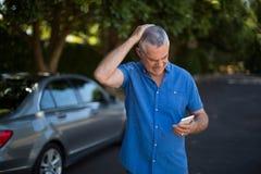 Gestraffter älterer Mann, der mit dem Auto Handy verwendet Lizenzfreies Stockfoto