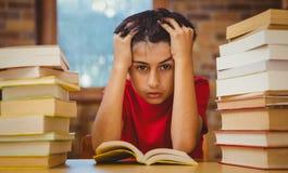 Gestraffter Junge, der mit Stapel Büchern sitzt Stockfoto