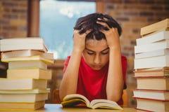 Gestraffter Junge, der mit Stapel Büchern sitzt Stockfotos