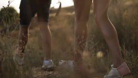 Gestreefde dichte omhooggaande lengte van wandelaar` s voeten die door heuvels lopen Mannelijke en vrouwelijke benen, die whire t stock video
