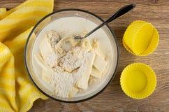 Gestreept servet, bloemmengsel met boter, melk voor muffins, lepel in kom, siliconevormen op houten lijst Hoogste mening royalty-vrije stock afbeelding