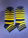 Gestreepte babysokken met zwarte en gele strepen royalty-vrije stock foto