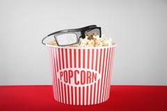 Gestreepte emmer met smakelijke popcorn en glazen stock afbeelding