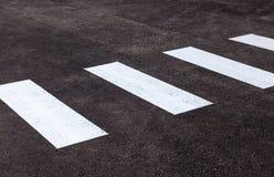 Gestreepte kruising met witte lijnen op asfalt Stock Foto
