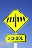 Gestreepte kruisingsverkeersteken met school Stock Fotografie