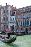 Gestreepte overhemdsgondelier die zijn Gondel, Venetië, Italië sturen stock fotografie
