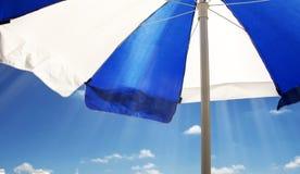 Gestreepte strandparaplu tegen de zon tegen de blauwe hemel Royalty-vrije Stock Foto