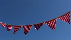 Gestreepte vlagbanner op het duidelijke blauwe skyblowing in de wind stock videobeelden