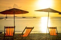 Gestreifte beachchairs und Sonnenschutz bei Sonnenuntergang stockbilder