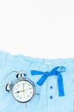 Gestreifte blaue Pyjamahosen und ein Wecker im Retrostil Stockfoto