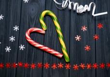 Gestreifte festliche Süßigkeiten im Herzen bilden sich mit Sternen und Serpentin auf dunkelblauem Weinlesehintergrund Lizenzfreie Stockbilder