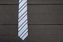 Gestreifte Geschäftsbindung auf hölzernem Hintergrund Lizenzfreies Stockfoto