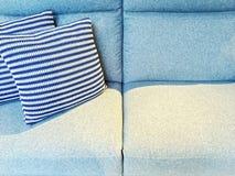 Gestreifte Kissen auf einem blauen Textilsofa Lizenzfreies Stockbild
