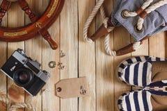 Gestreifte Pantoffel, Kamera, Tasche und Seedekorationen auf dem hölzernen Hintergrund Stockfotos