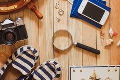 Gestreifte Pantoffel, Kamera, Tasche und Seedekorationen auf dem hölzernen Hintergrund Lizenzfreie Stockbilder