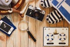 Gestreifte Pantoffel, Kamera, Tasche und Seedekorationen auf dem hölzernen Hintergrund Lizenzfreies Stockfoto