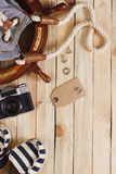 Gestreifte Pantoffel, Kamera, Tasche und Seedekorationen auf dem hölzernen Hintergrund Lizenzfreies Stockbild