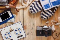 Gestreifte Pantoffel, Kamera, Tasche und Seedekorationen auf dem hölzernen Hintergrund Stockbilder