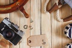 Gestreifte Pantoffel, Kamera, Tasche und Seedekorationen auf dem hölzernen Hintergrund Stockfotografie