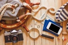 Gestreifte Pantoffel, Kamera, Tasche und Seedekorationen auf dem hölzernen Hintergrund Stockbild