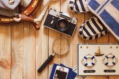 Gestreifte Pantoffel, Kamera, Tasche und Seedekorationen auf dem hölzernen Hintergrund Lizenzfreie Stockfotos