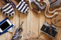 Gestreifte Pantoffel, Kamera, Telefon und Miniatur des Freiheitsstatuen auf dem hölzernen Hintergrund Stockbild