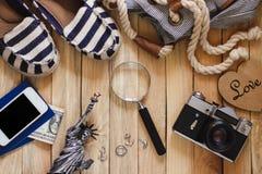 Gestreifte Pantoffel, Kamera, Telefon und Miniatur des Freiheitsstatuen, hölzerner Hintergrund Lizenzfreie Stockbilder