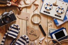 Gestreifte Pantoffel, Kamera, Telefon und Seedekorationen auf dem hölzernen Hintergrund Stockfotos