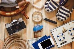 Gestreifte Pantoffel, Sparschwein, Telefon und Seedekorationen, hölzerner Hintergrund Lizenzfreies Stockbild