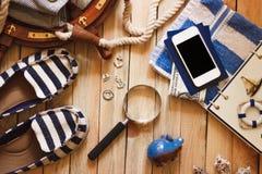 Gestreifte Pantoffel, Tuch, Sparschwein, Telefon und Seedekorationen, hölzerner Hintergrund Lizenzfreie Stockfotos