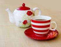 gestreifte Schale mit Tee auf einer Untertasse und einem Brauer mit einem Mohnblumenbild Stockfoto