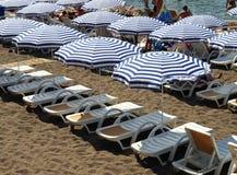 Gestreifte Strandschirme und weiße sunbeds Lizenzfreies Stockbild