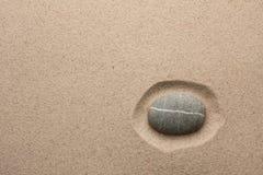Gestreifter grauer Stein, der im Sand liegt Stockbild