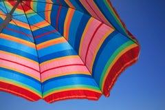 Gestreifter Regenschirm gegen einen blauen Himmel Stockbild