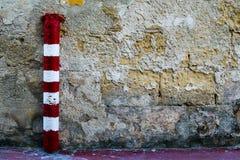 Gestreifter roter und weißer Pfosten gegen eine strukturierte Wand Stockbild