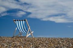 Gestreiftes deckchair auf Pebble Beach Lizenzfreie Stockfotos