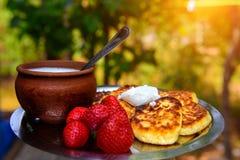 Gestremde melkfritters met zure room en aardbeien, eigengemaakte traditionele Oekraïense en Russische syrniki op vage groene acht stock afbeelding